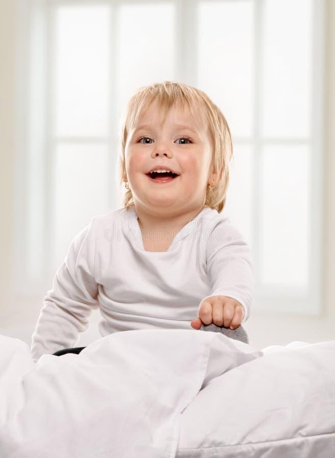 Bambino felice della neonata che gioca a letto immagini stock