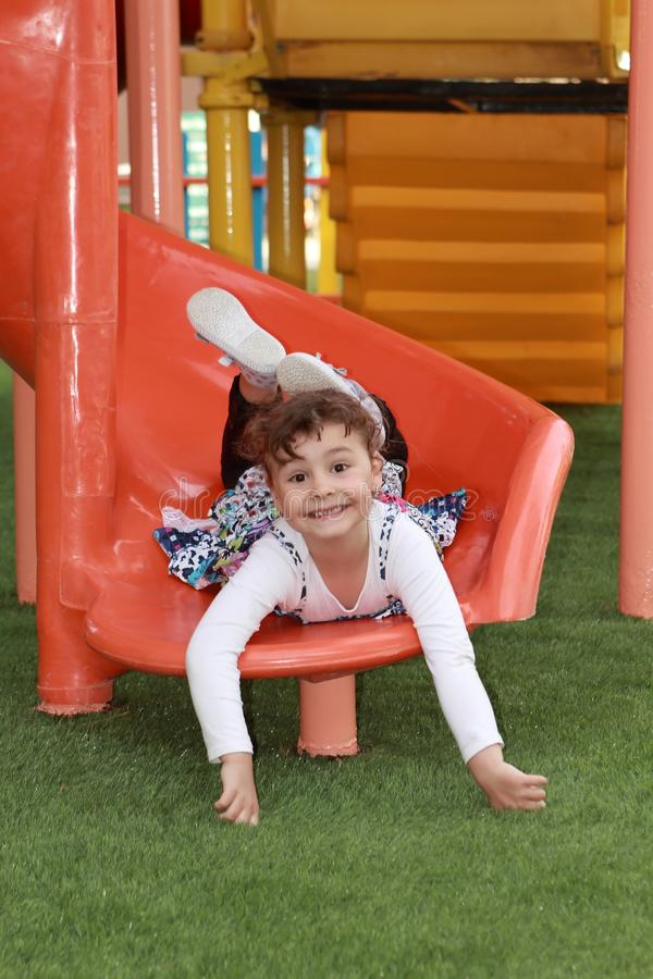 Bambino felice nel campo da giuoco del parco fotografie stock