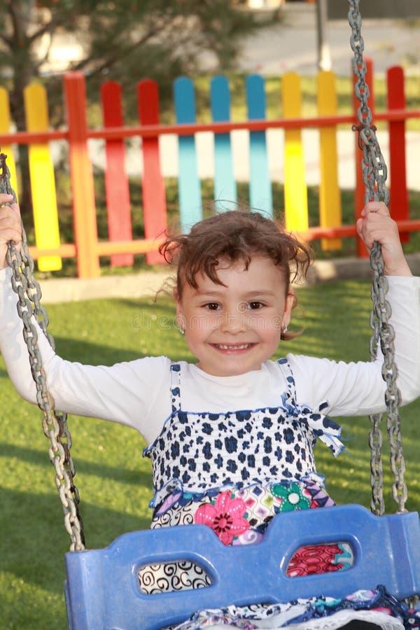 Bambino felice nel campo da giuoco del parco immagine stock libera da diritti