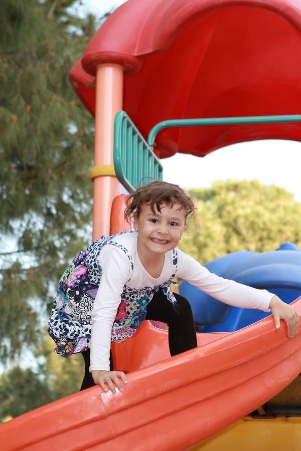 Bambino felice nel campo da giuoco del parco immagine stock