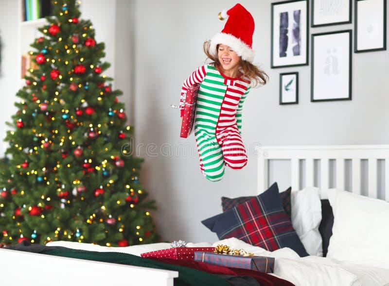 Bambino felice in pigiami con i regali che saltano a letto sul natale m. immagini stock