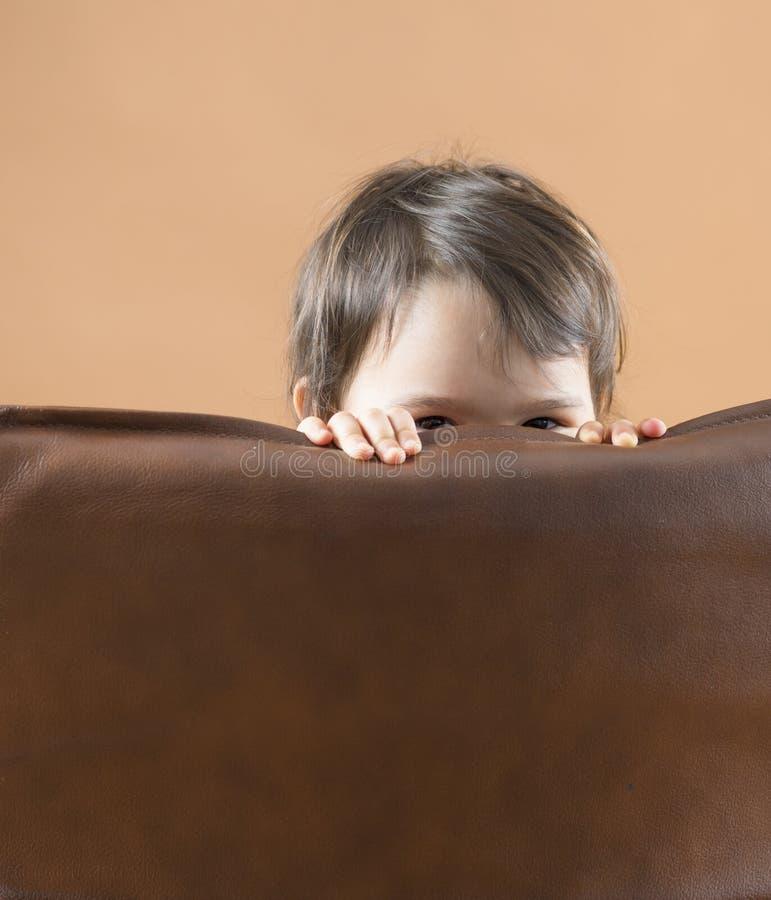 Bambino felice, ragazza sveglia che gioca e che si nasconde dietro il sofà fotografie stock libere da diritti