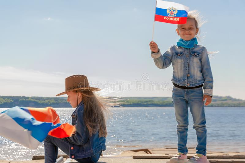 Bambino felice, ragazza sveglia del piccolo bambino con la bandiera della Russia contro un chiaro cielo blu fotografia stock libera da diritti