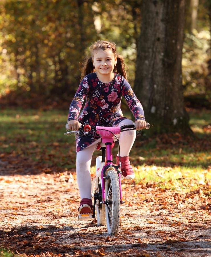 Bambino felice sulla bici nella foresta di autunno immagine stock