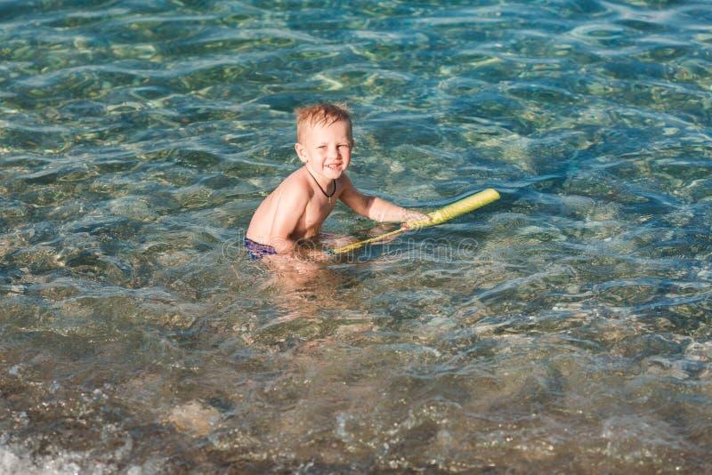 Bambino felice sveglio che gioca con la pistola di acqua fotografia stock