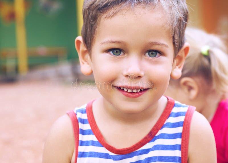 Bambino felice sveglio divertente che gioca sul campo da giuoco L'emozione di felicità, divertimento, gioia Sorriso di un ragazzo fotografia stock