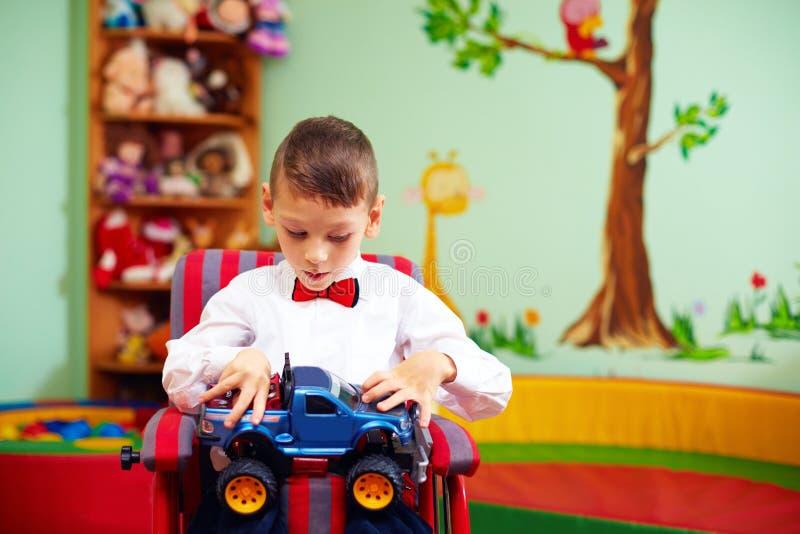 Bambino felice sveglio sulla sedia a rotelle con il presente nell'asilo per i bambini con i bisogni speciali fotografia stock libera da diritti