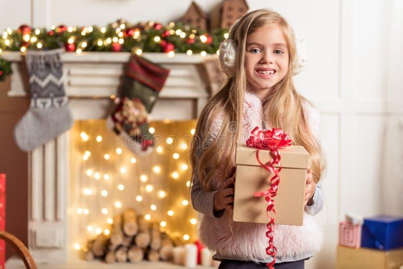 Bambino femminile emozionante che tiene il regalo di festa immagine stock