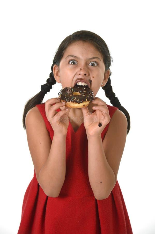 Bambino femminile ispano in vestito rosso che mangia la ciambella del cioccolato con le mani e bocca macchiata e sorridere sporco immagini stock libere da diritti