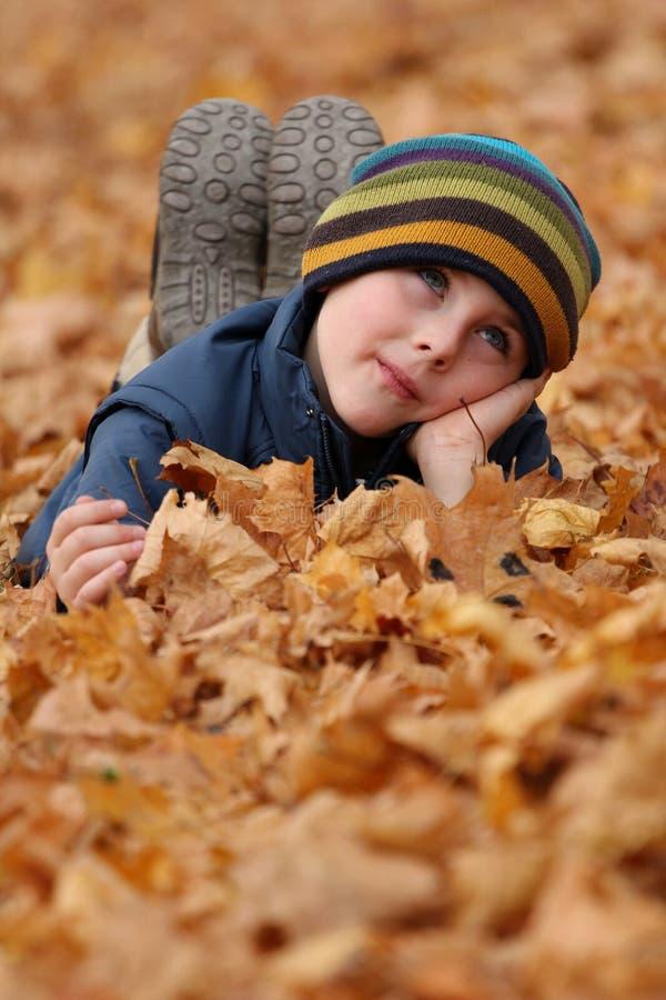Bambino in fogli di autunno fotografie stock libere da diritti