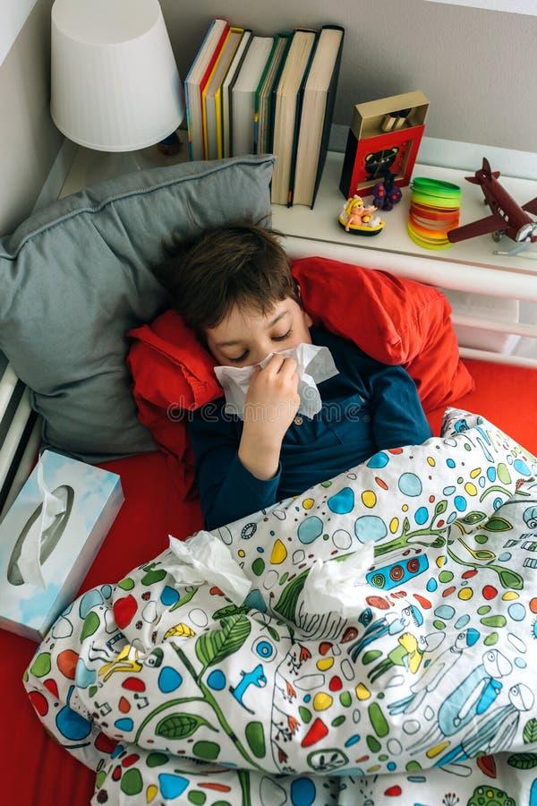 Bambino freddo che si trova sul letto immagine stock libera da diritti