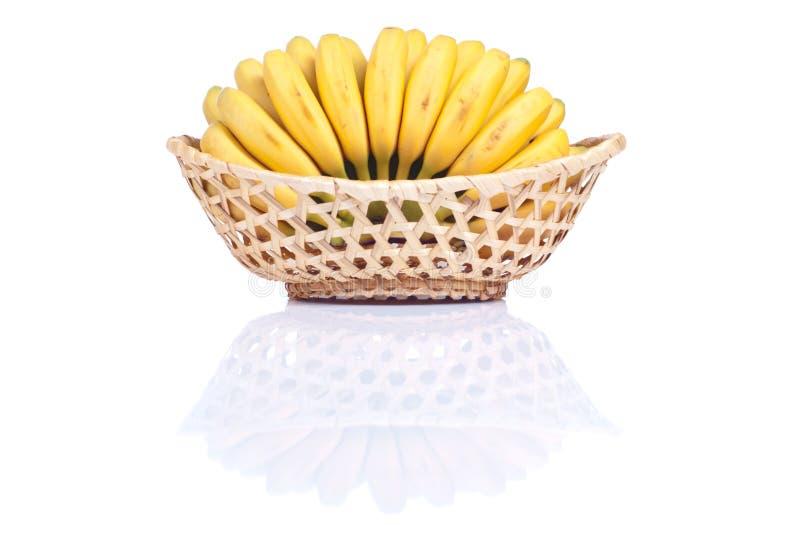 Bambino giallo maturo delle banane in un canestro di vimini isolato sulle sedere bianche immagini stock libere da diritti