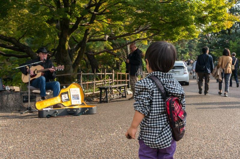 Bambino giapponese con il musicista occidentale fotografia stock