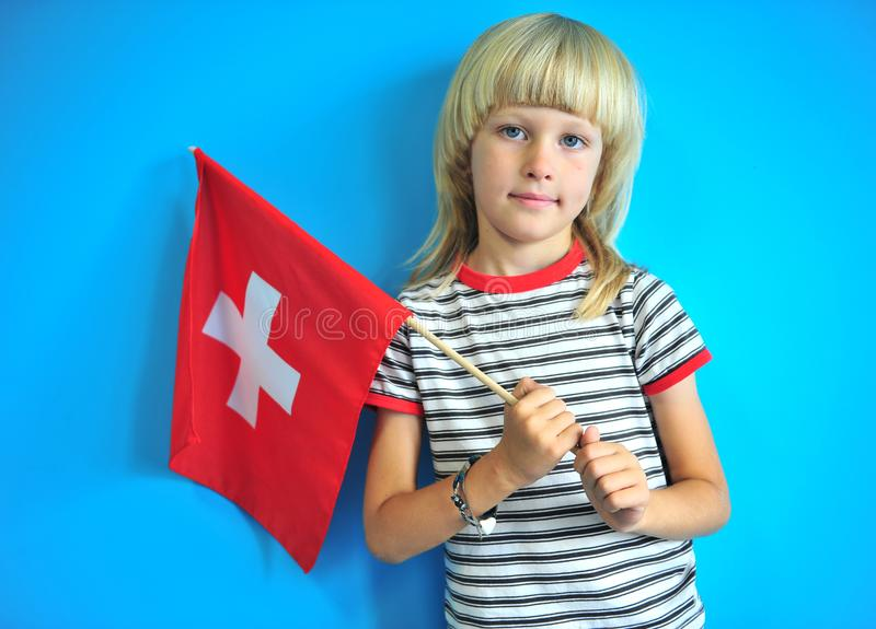 Bambino grazioso con una bandiera nazionale della Svizzera immagini stock libere da diritti