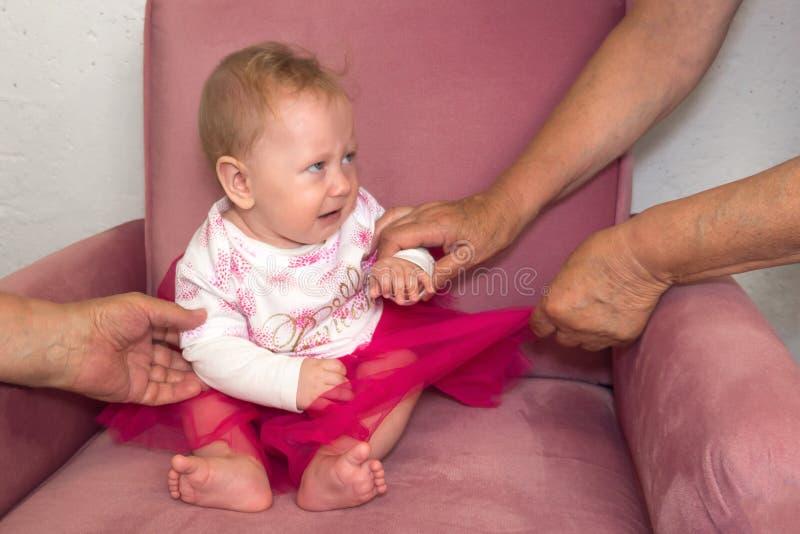 Bambino gridante Mani degli adulti, genitori che provano a calmare gridare bambino immagini stock