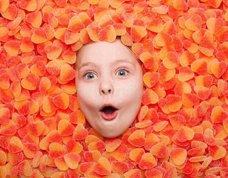 Bambino impressionato che posa in gelatina di frutta fotografia stock libera da diritti