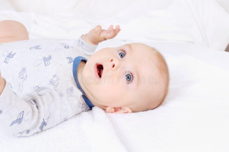 Bambino infantile del bambino divertente con gli occhi azzurri che si trovano sul letto immagini stock