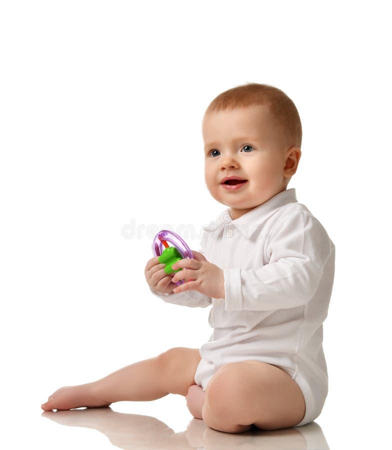 Bambino infantile del ragazzo del bambino che si siede con il giocattolo di plastica isolato immagini stock libere da diritti