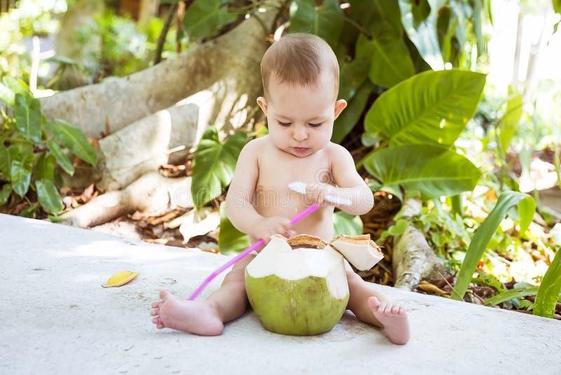 Bambino infantile pensieroso ed appassionato alla vacanza tropicale Mangia e beve la giovane noce di cocco verde con il cucchiaio immagine stock