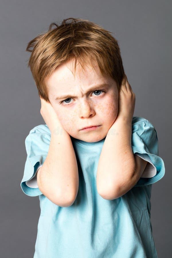Bambino infelice che aborre la sua istruzione, proteggente le sue orecchie chiuse immagine stock libera da diritti