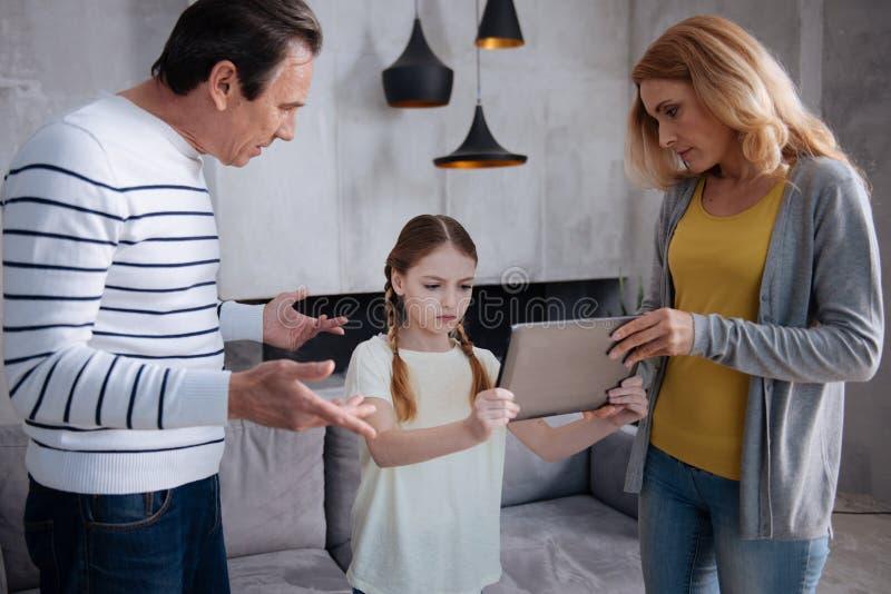 Bambino interessato di educazione dei genitori a casa immagini stock libere da diritti