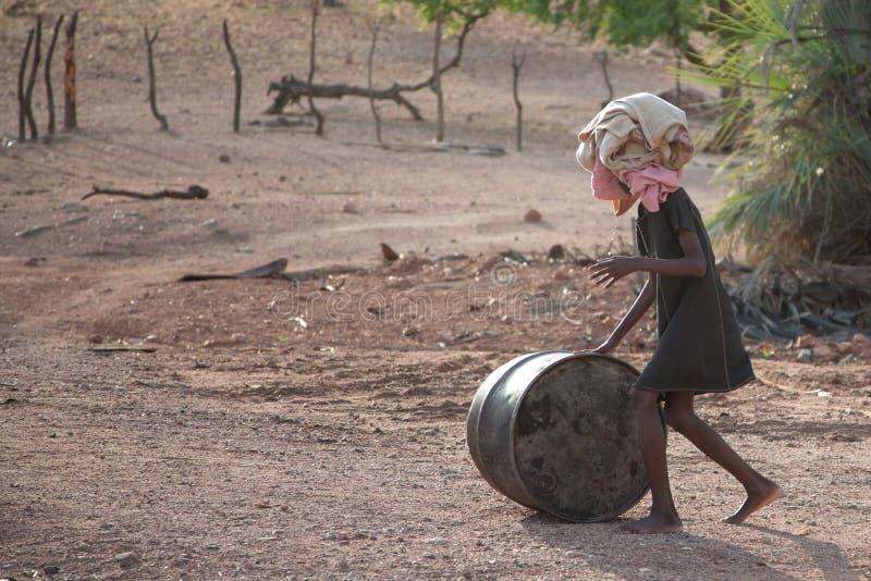Bambino locale povero che cammina con un barilotto ed i vestiti su lei capa dentro immagine stock libera da diritti