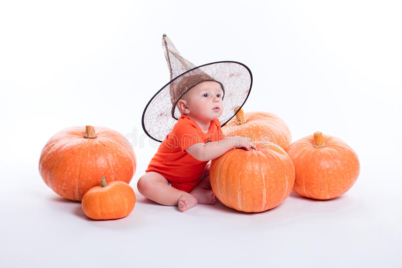 Bambino in maglietta arancio su un fondo bianco che si siede in un witche immagini stock libere da diritti