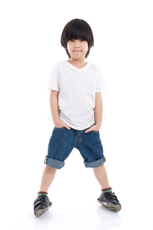 Bambino in maglietta bianca e jeans che stanno sul fondo bianco immagine stock