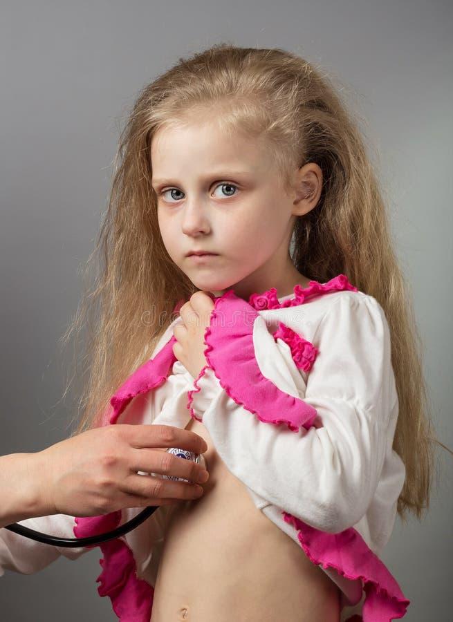 Bambino malato alla ricezione del ` s di medico, su gray immagini stock