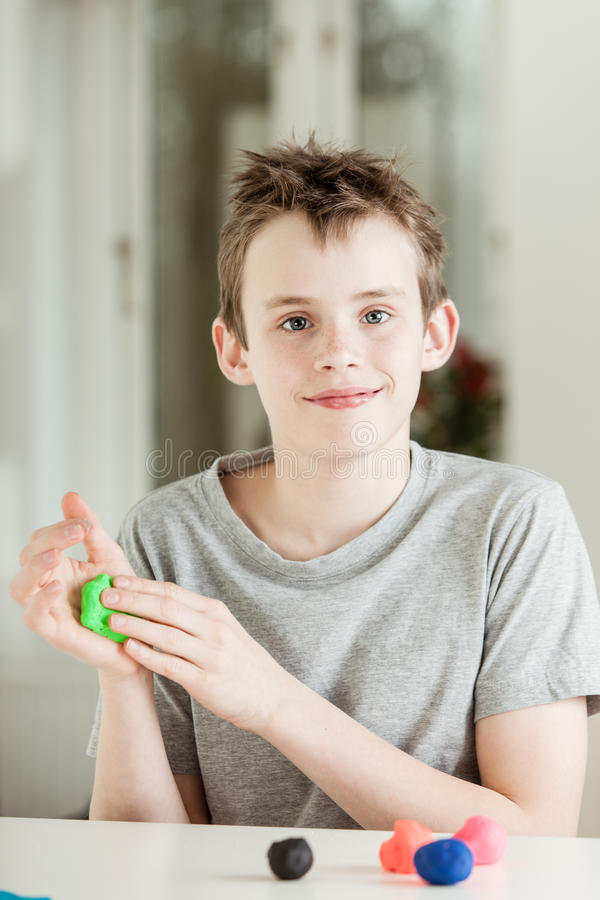 Bambino maschio felice che lavora con l'argilla verde fotografia stock