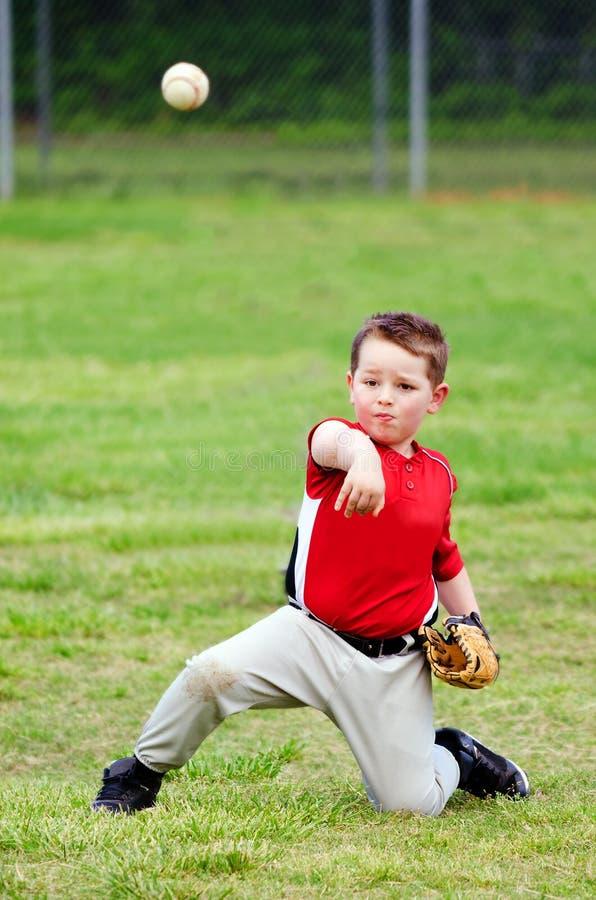 Bambino nel baseball di lancio dell'uniforme fotografia stock