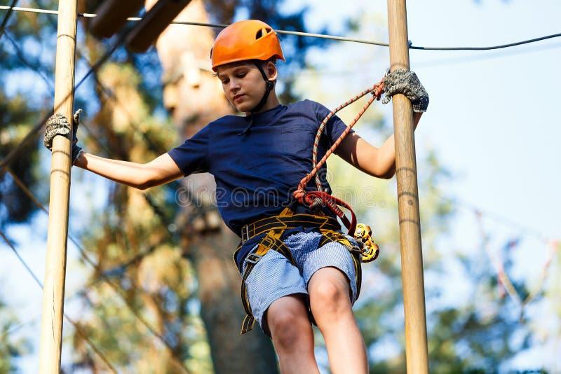 Bambino nel parco di avventura della foresta Bambino in casco arancio e salite blu della maglietta sull'alta traccia della corda  immagine stock