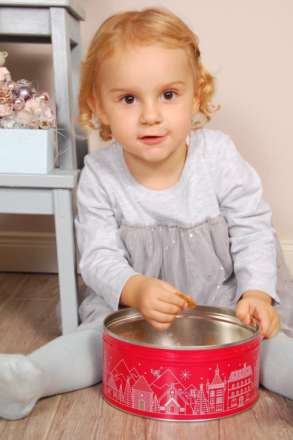 Bambino nella cucina che si siede e che mangia i biscotti sotto forma di un rettangolo fotografia stock