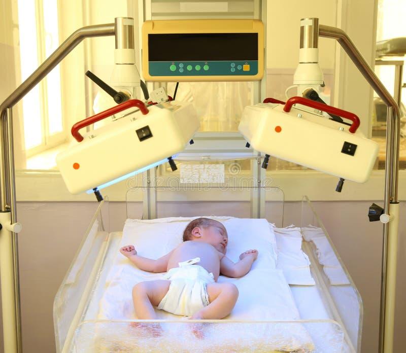 Bambino neonato sotto le lampade ultraviolette immagine stock
