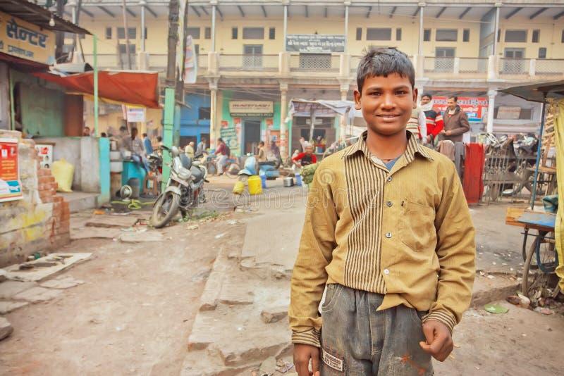 Bambino non identificato in vestiti sporchi che stanno sulla povera via indiana fotografie stock libere da diritti