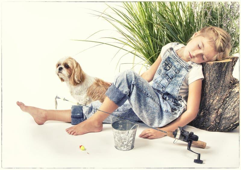 Bambino o ragazza con il suo cane che prende un pelo o che dorme mentre immagine stock libera da diritti