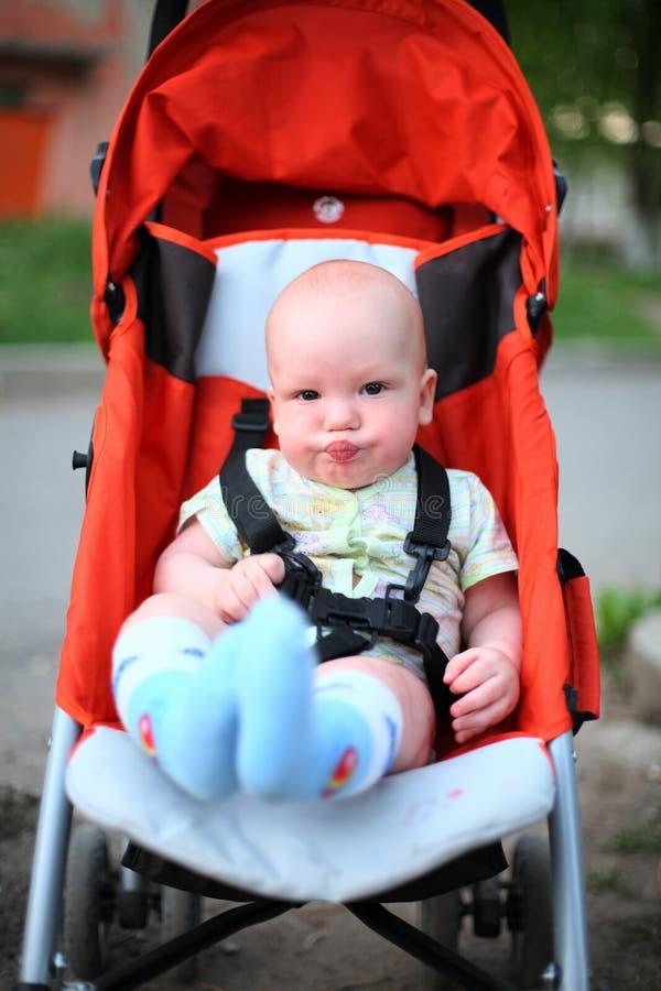 Bambino in passeggiatore di seduta immagini stock libere da diritti