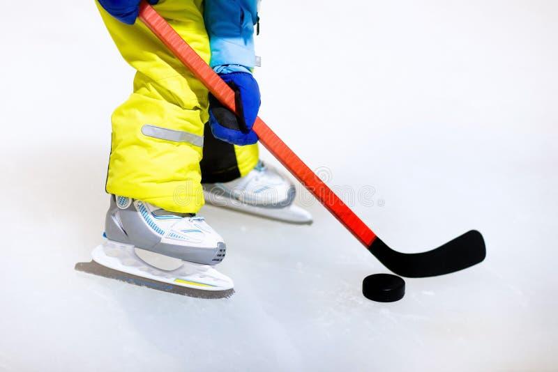 Bambino in pattini che giocano hockey su ghiaccio sulla pista di pattinaggio dell'interno fotografia stock libera da diritti