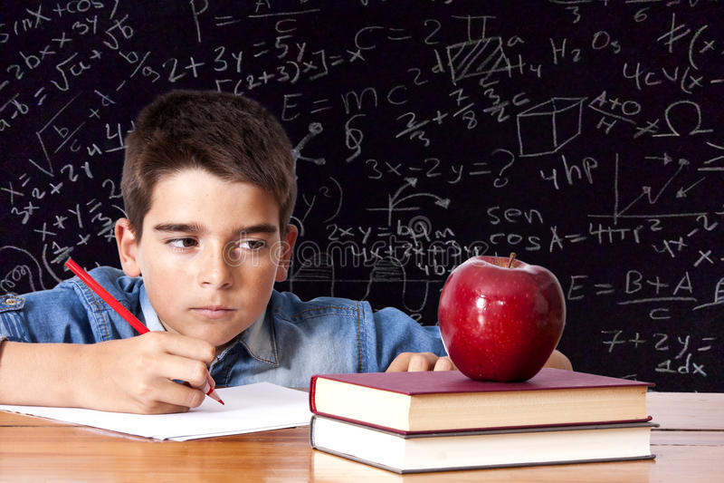 Bambino pensieroso a scuola immagini stock