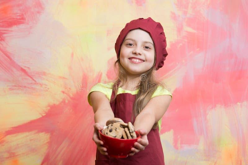 Bambino, piccola ragazza in cappello rosso del cuoco unico, grembiule con i biscotti del cioccolato fotografia stock libera da diritti