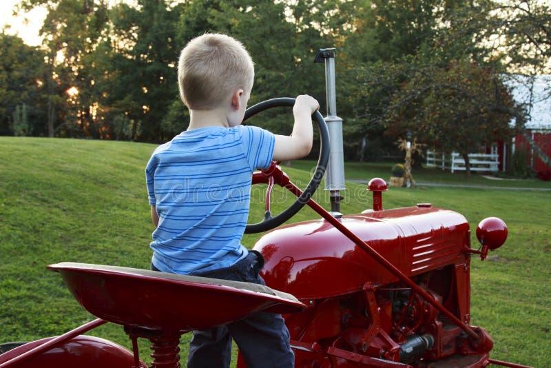 Bambino piccolo che finge di guidare il trattore antico rosso fotografia stock libera da diritti