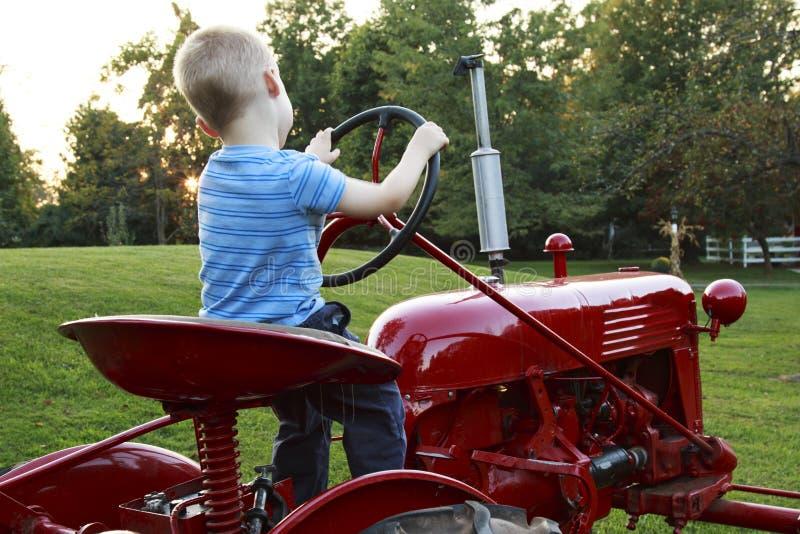 Bambino piccolo che finge di guidare un trattore rosso immagine stock