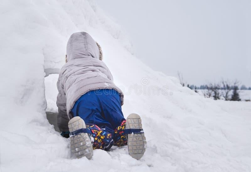 Bambino piccolo che striscia in una configurazione forte della neve in un cortile Pellame - e - ricerca Divertimento di inverno fotografie stock libere da diritti