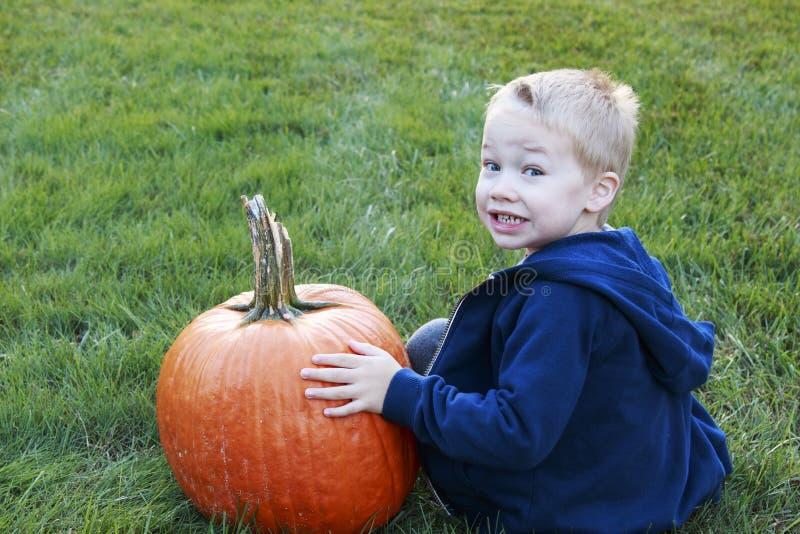 Bambino piccolo che tiene la sua grande zucca per Halloween in un erboso fotografia stock libera da diritti