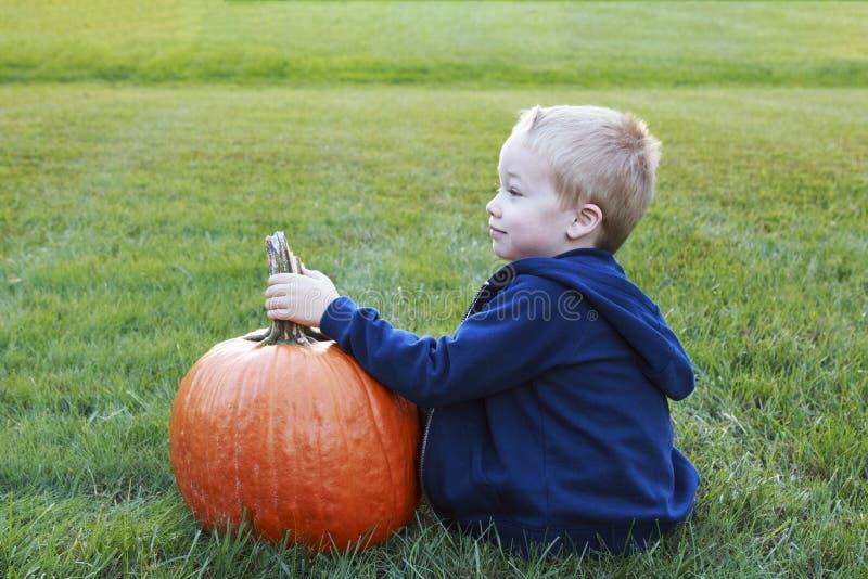 Bambino piccolo che tiene la sua grande zucca per Halloween in un erboso fotografie stock libere da diritti