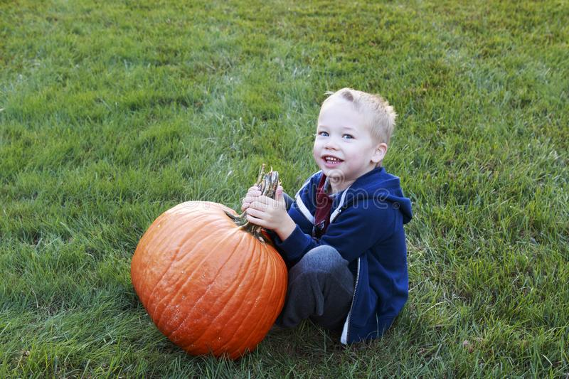 Bambino piccolo che tiene la sua zucca in un campo erboso fotografia stock libera da diritti