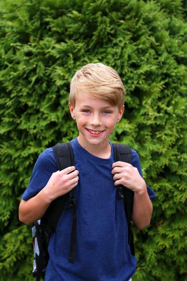Bambino piccolo con Backback che si prepara per il suo primo giorno di scuola nel quarto grado fotografia stock libera da diritti