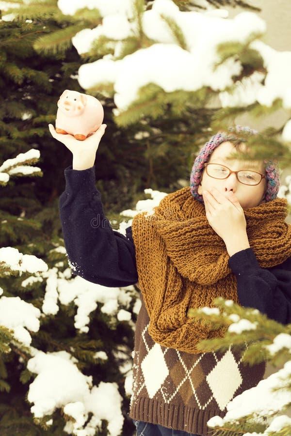 Bambino piccolo con il salvadanaio nell'inverno all'aperto immagini stock libere da diritti