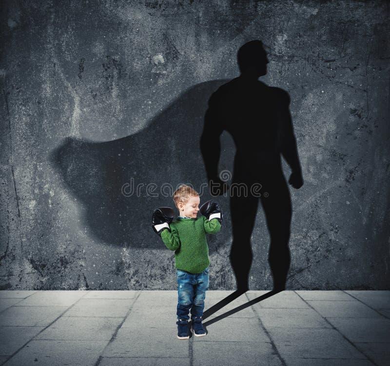 Bambino piccolo con la sua ombra dell'eroe eccellente sulla parete fotografie stock libere da diritti