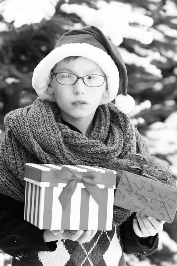 Bambino piccolo con le scatole attuali nell'inverno all'aperto fotografia stock